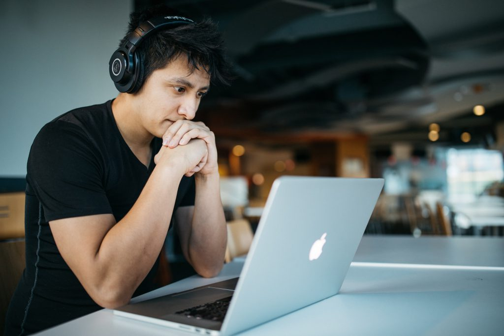 Boy with headphones using a MacBook